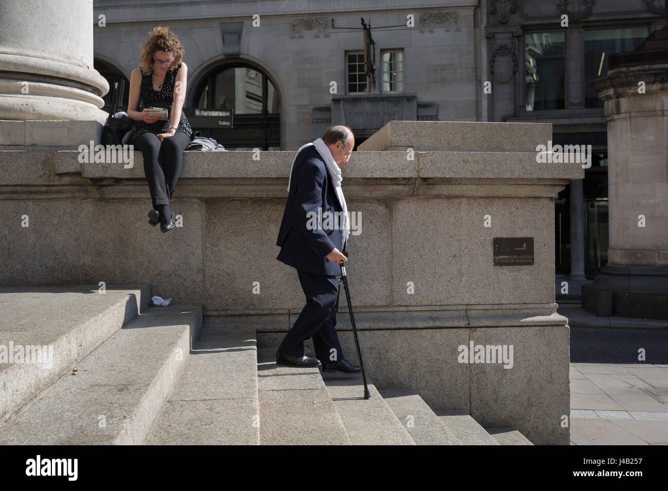 Using walking sticks, an elderly gentleman gently walks down the steps of Royal Exchange at Bank Triangle, on 10th - Stock Image