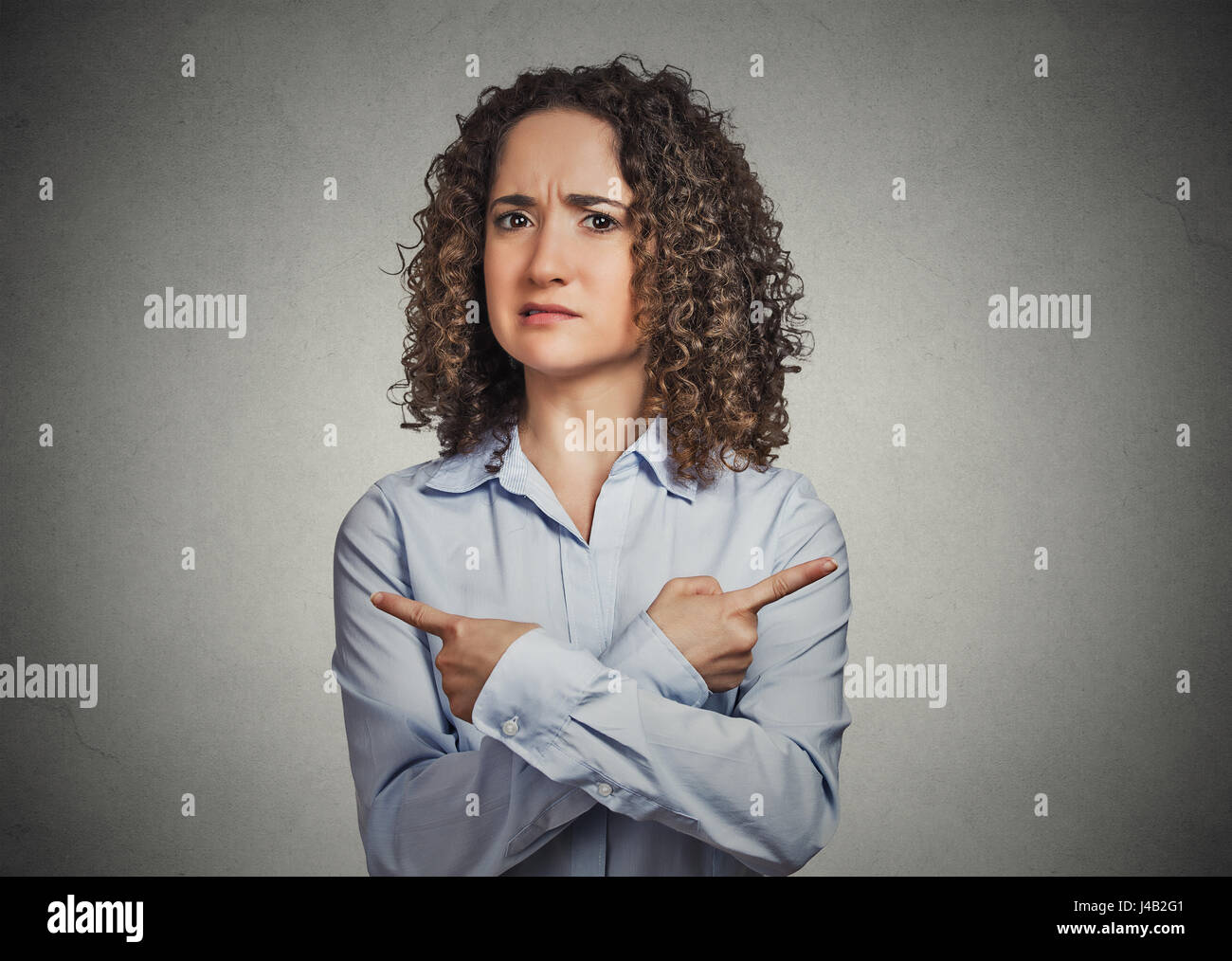 Indecision confusion. Portrait confused young woman pointing in two different directions not sure which way to go - Stock Image
