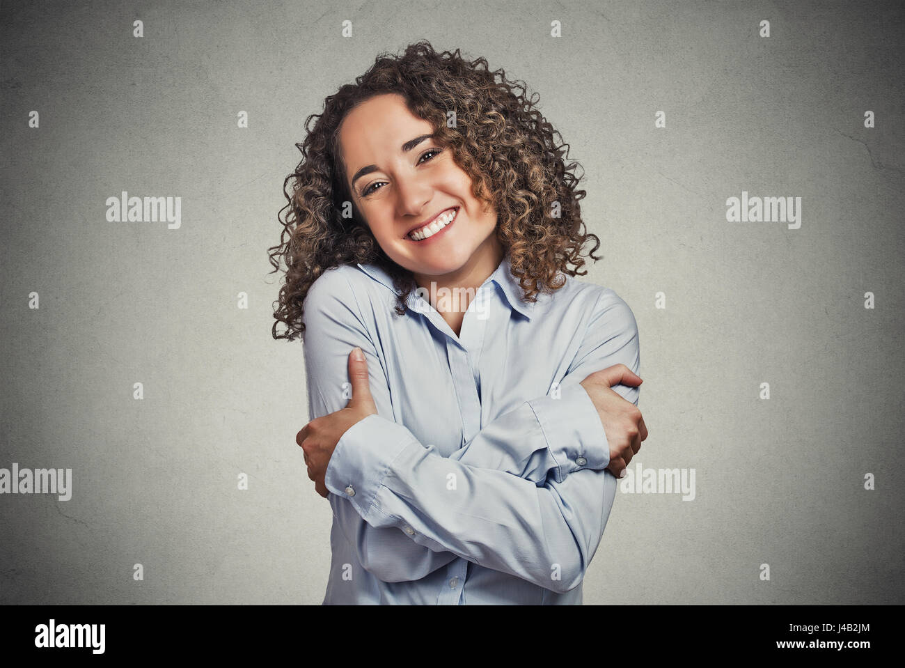 Closeup portrait confident smiling woman holding hugging herself isolated grey wall background. Positive human emotion, - Stock Image