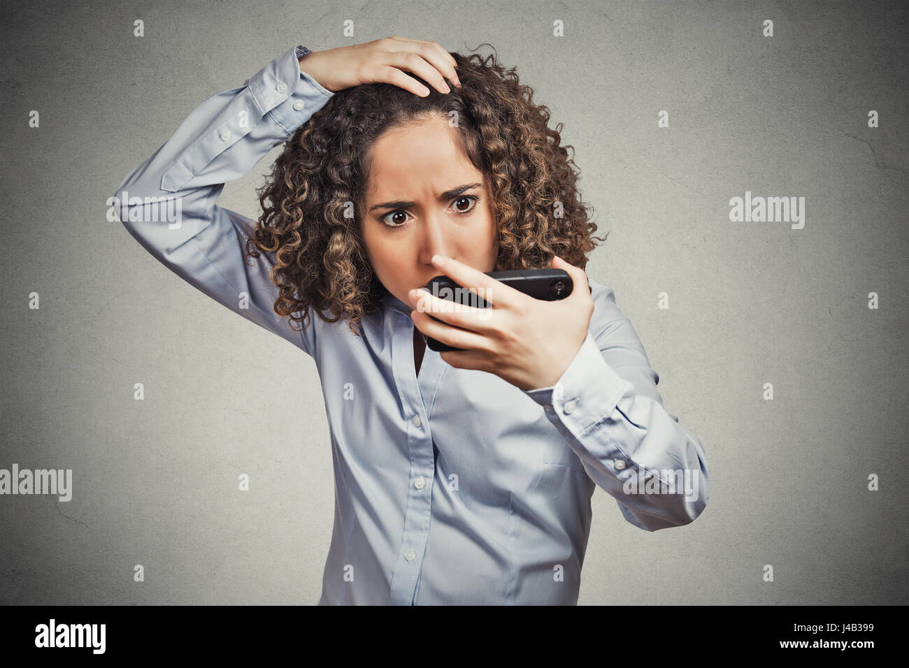 Closeup portrait shocked funny looking young woman, feeling head, surprised she is losing hair has receding hairline Stock Photo