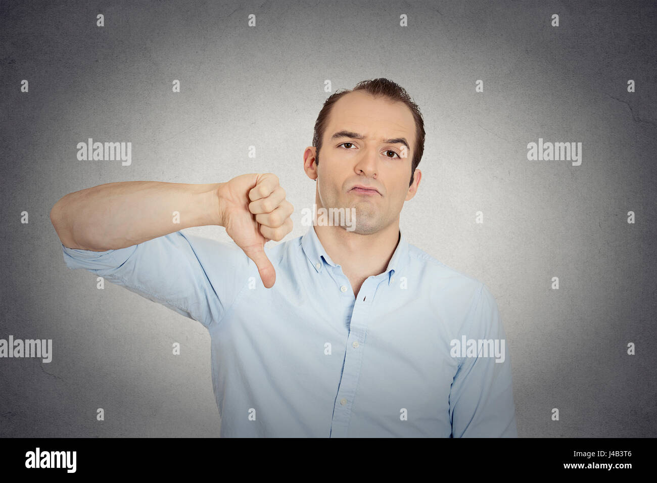 Closeup portrait of angry, unhappy, young handsome man showing thumbs down sign, in disapproval of offer, situation - Stock Image