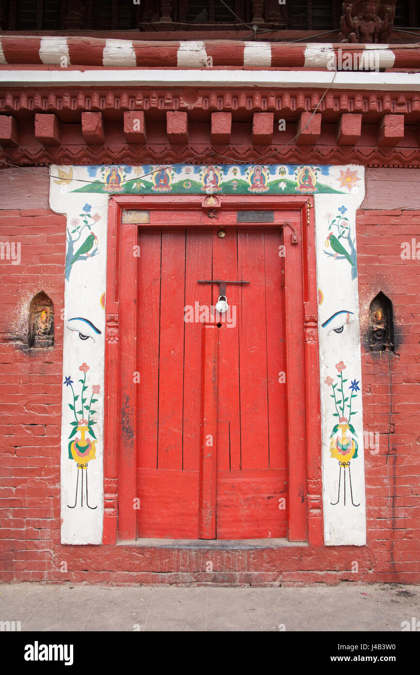 Red door with a decorative surround, entrance to a house in Patan or Lalitpur Kathmandu, Nepal Stock Photo