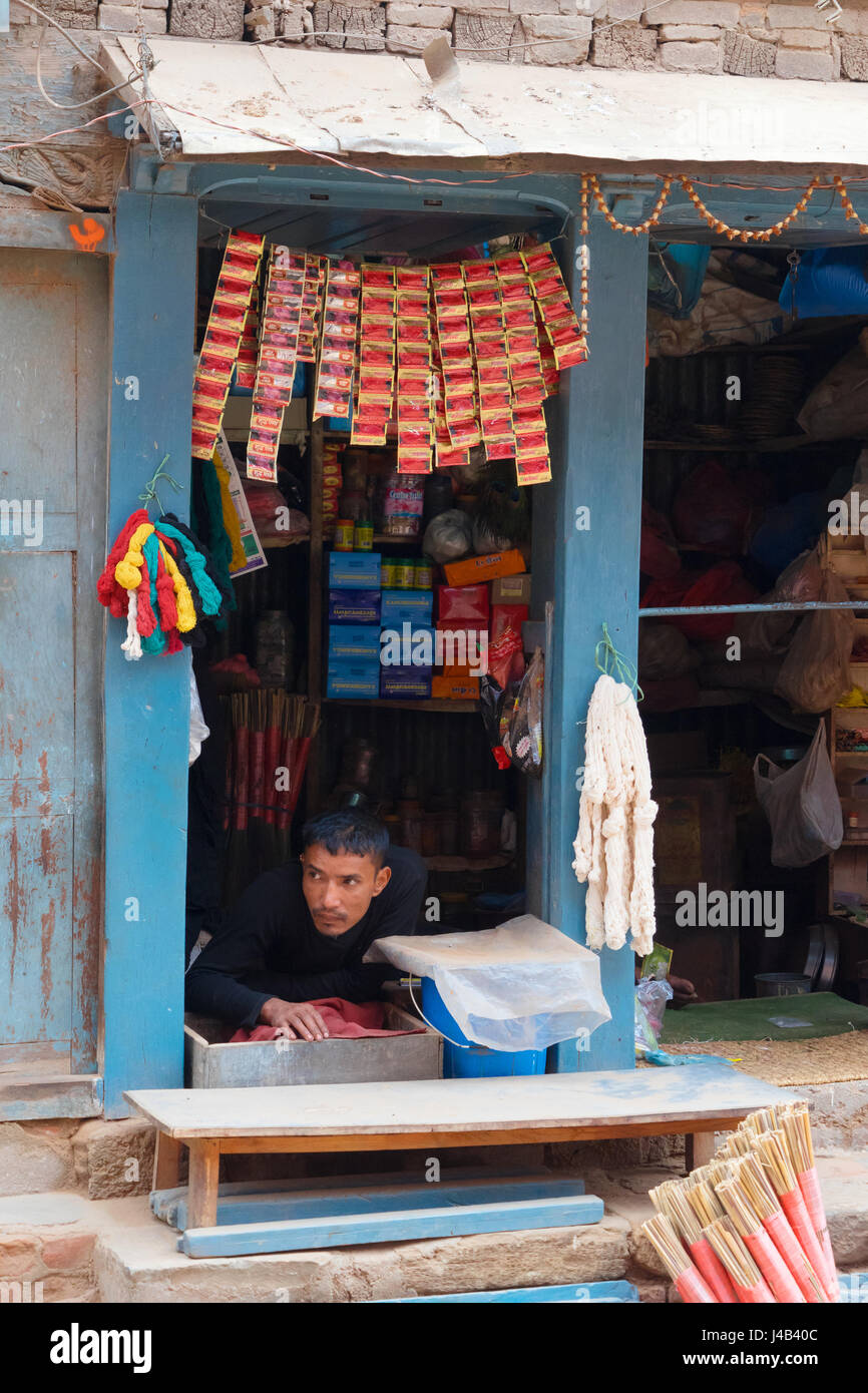 Disabled shop owner is waiting for customers, lying flat on his belly. Bhaktapur, Nepal. - Stock Image