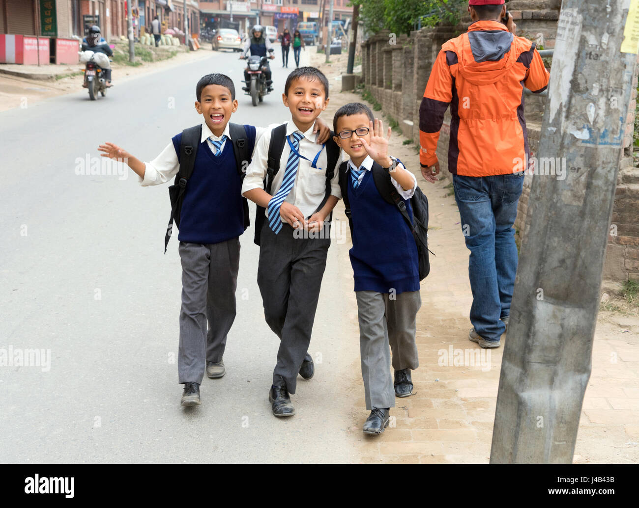 Smiling Nepalese schoolboys in uniforms walking on the street, Bhaktapur. Stock Photo