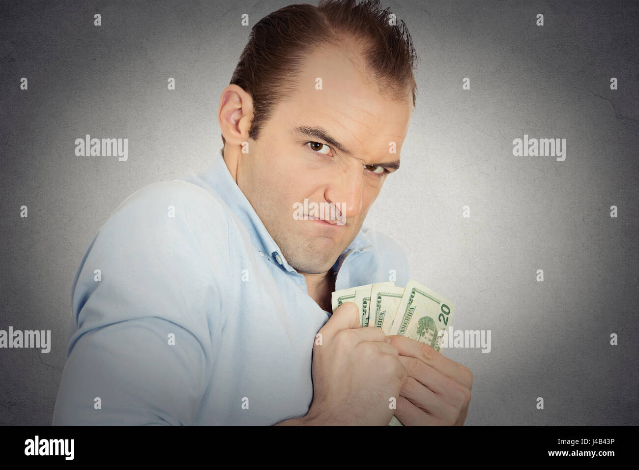 Closeup portrait greedy banker executive CEO boss, corporate employee funny looking man holding dollar banknotes - Stock Image