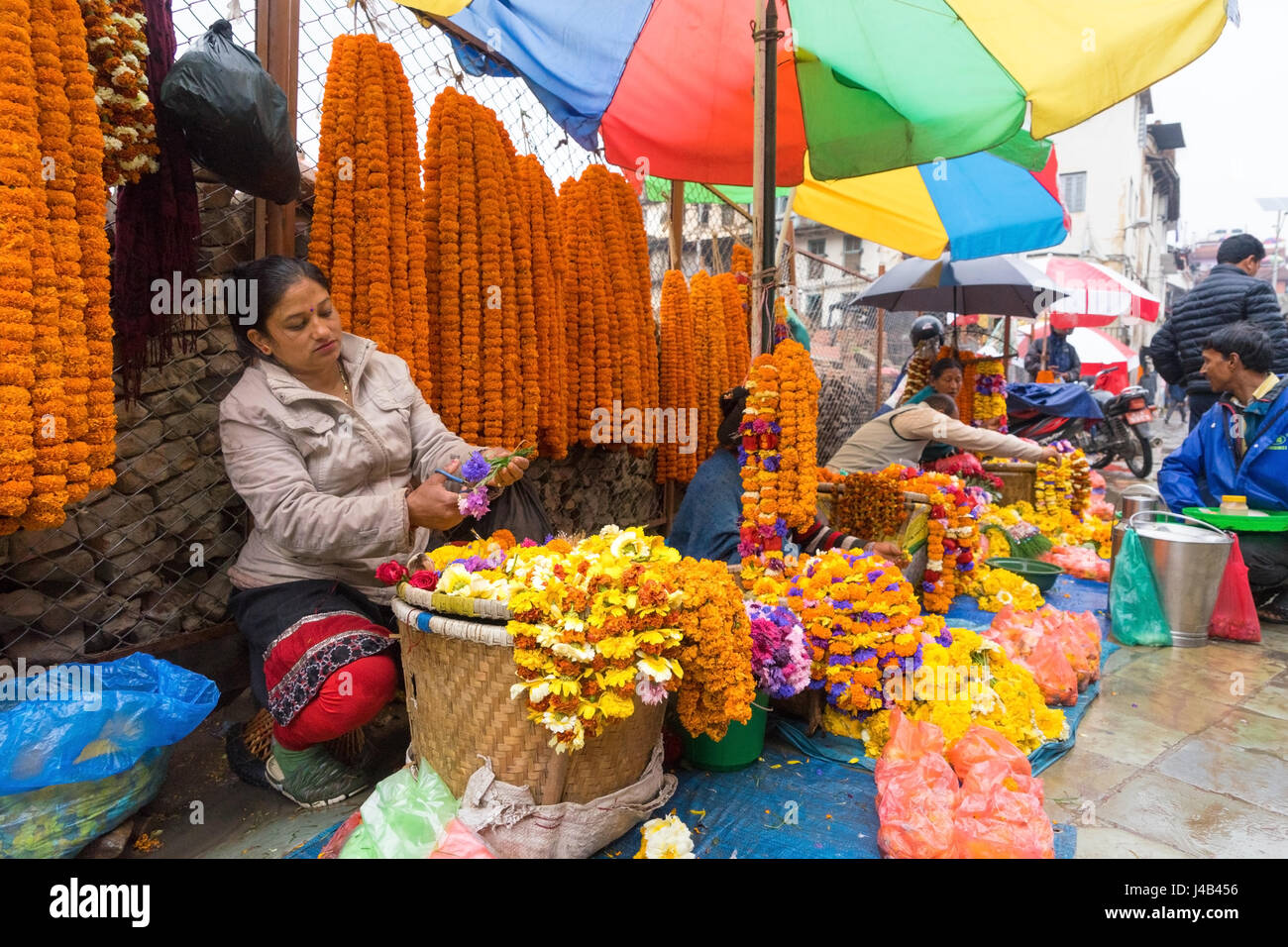 Flower saleswoman preparing a necklace. Kathmandu, Nepal. - Stock Image