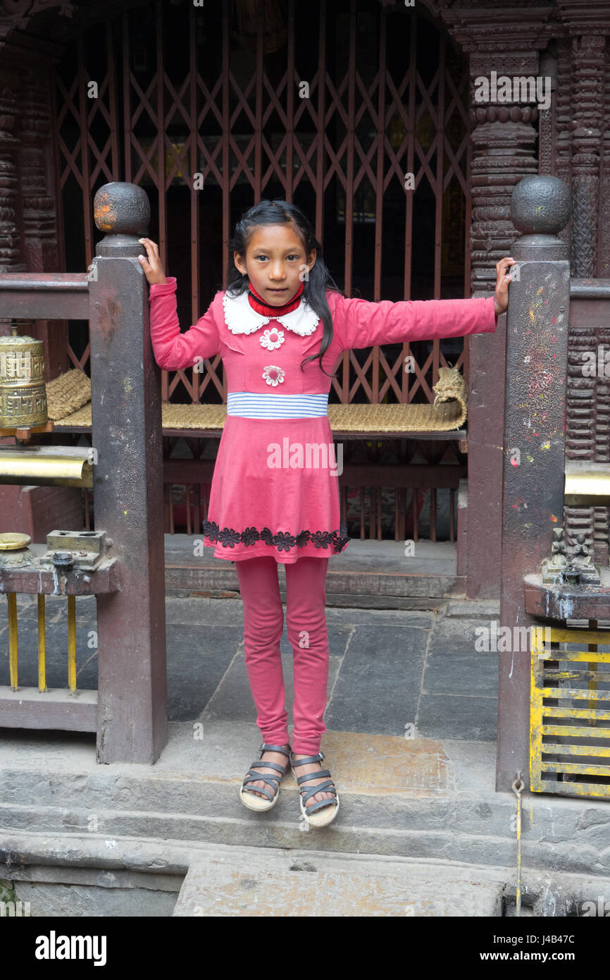 Young Nepalese girl dressed in pink, Golden Temple,Kathmandu. - Stock Image