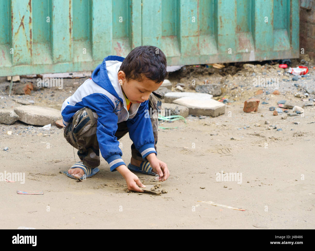 Young Nepalese boy playing with sand in Khatmandu. - Stock Image