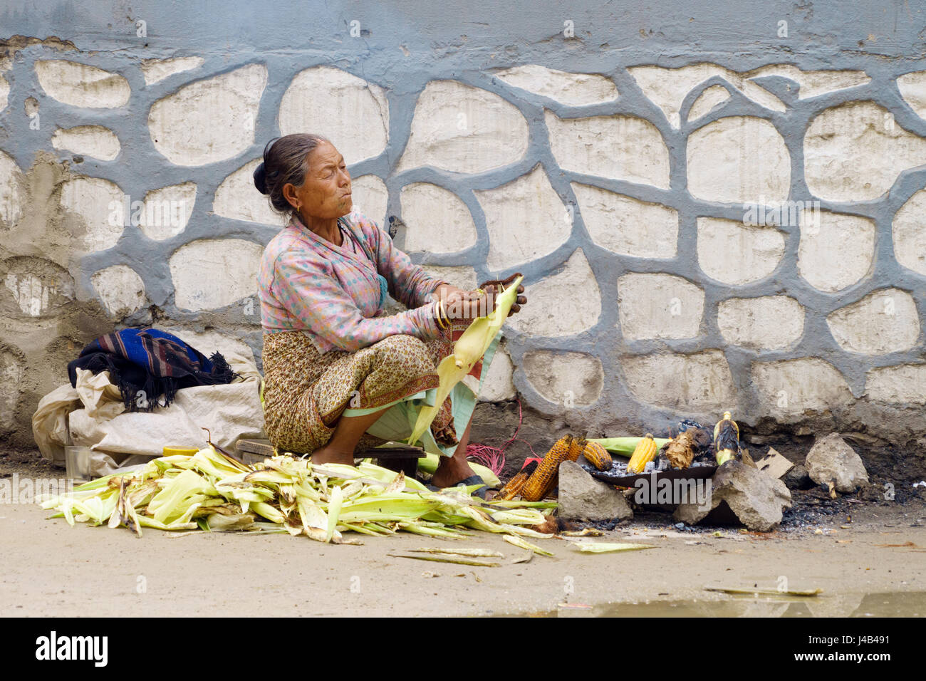 Old indigent woman roasting corn on the side of the street in heavily polluted air. Kathmandu, Nepal. - Stock Image