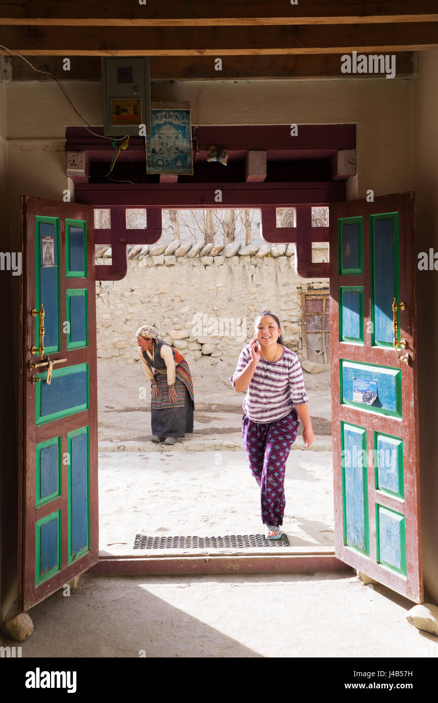Tibetan teenaged girl speaking on cell phone and older woman dressed in traditional clothes in the background. - Stock Image