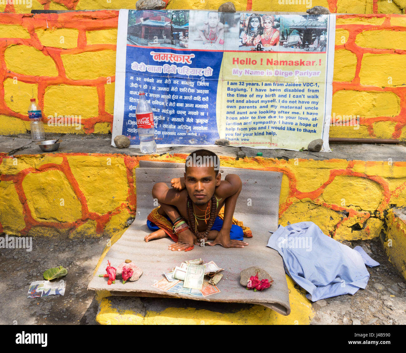 Victim of poliomyelitis begging in Pokhara, Nepal. - Stock Image
