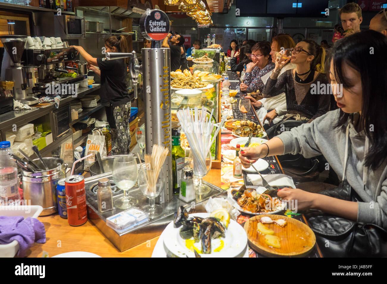 People sitting at the bar eating seafood tapas in Mercat de Sant Josep de la Boqueria, Barcelona Spain. - Stock Image