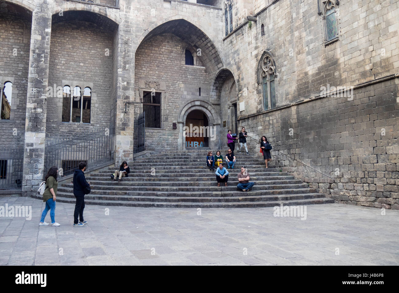 People sitting the steps leading to the Saló del Tinell and the Chapel of St. Agatha at Placa del Rei, Barcelona, - Stock Image