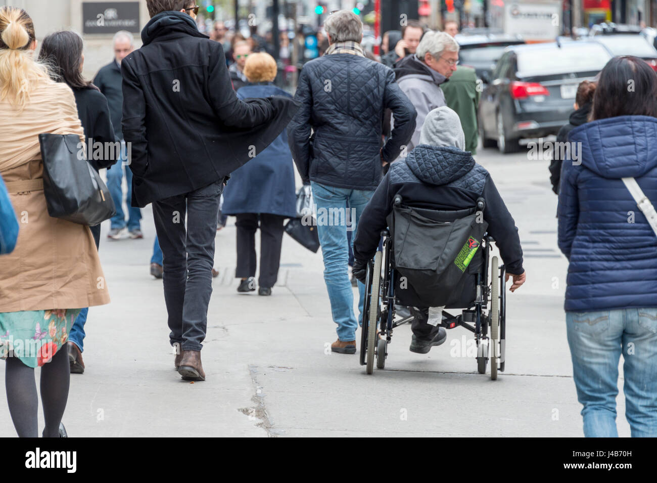Disabled man sitting in a wheelchair on a busy street among crowd of people - Stock Image