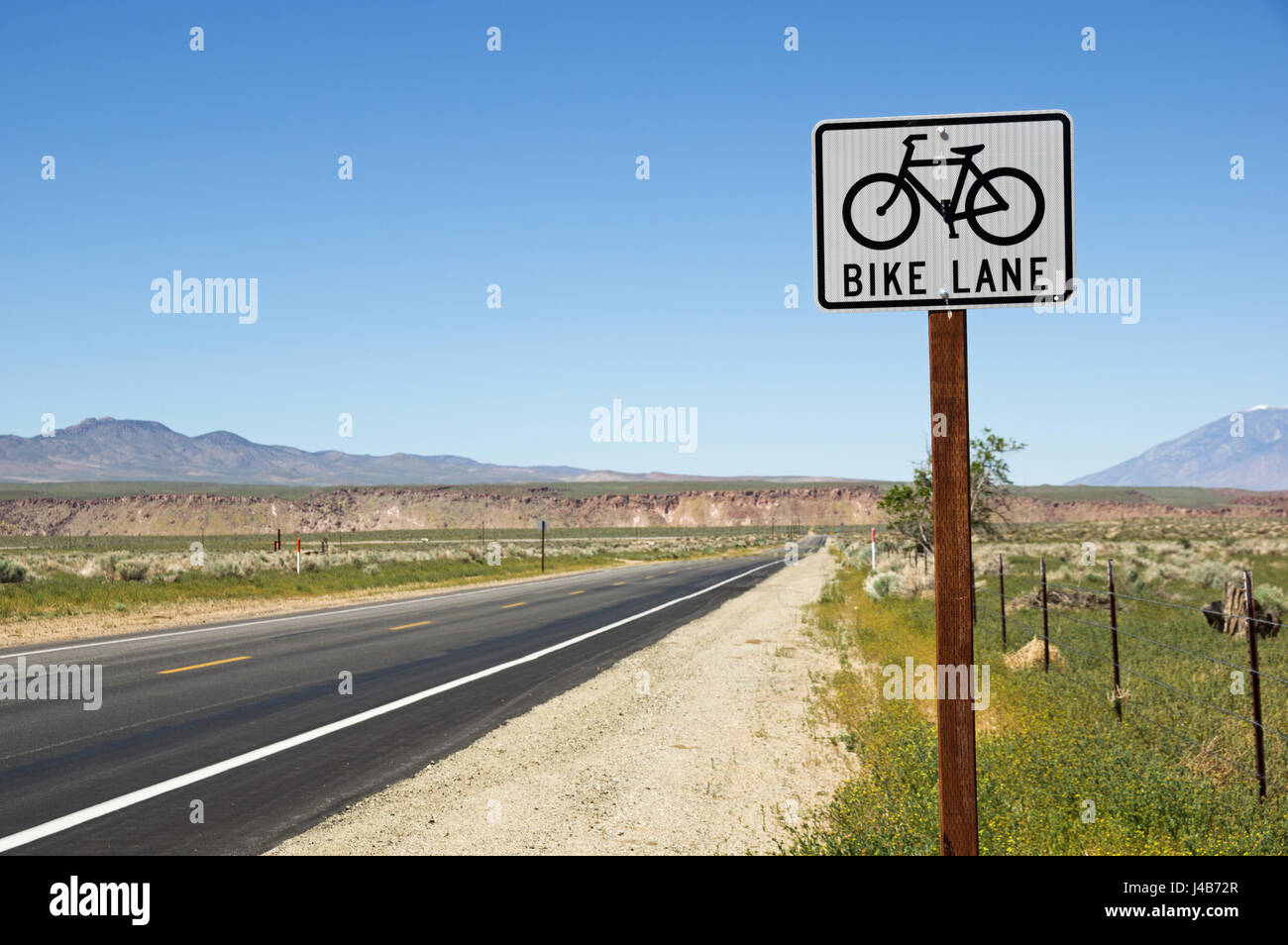 bike lane sign on the side of straight road in the Owens Valley countryside - Stock Image