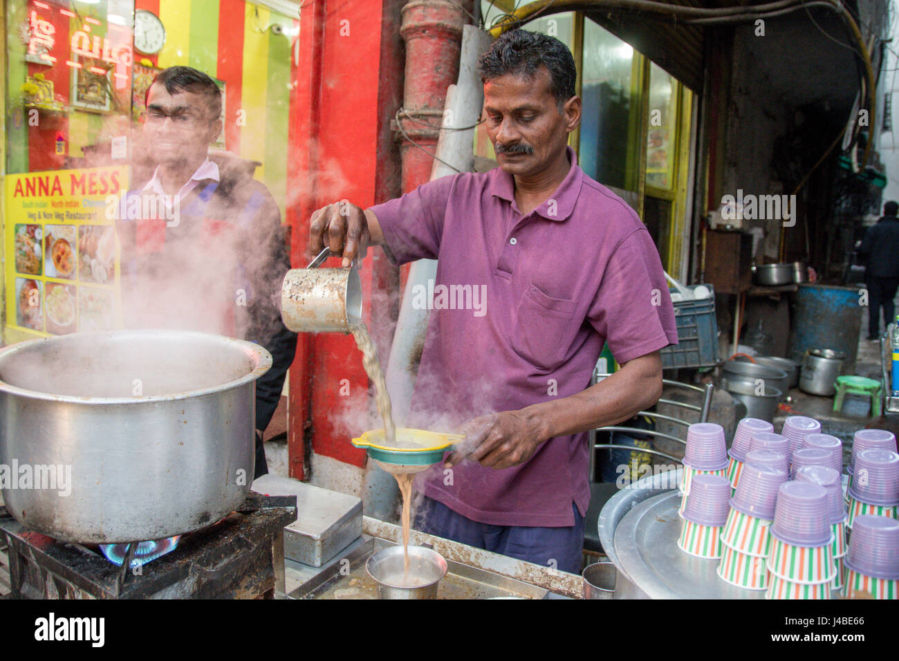 Man pouring a hot beverage through a sifter before serving at the Khari Baoli market in New Delhi, India. - Stock Image
