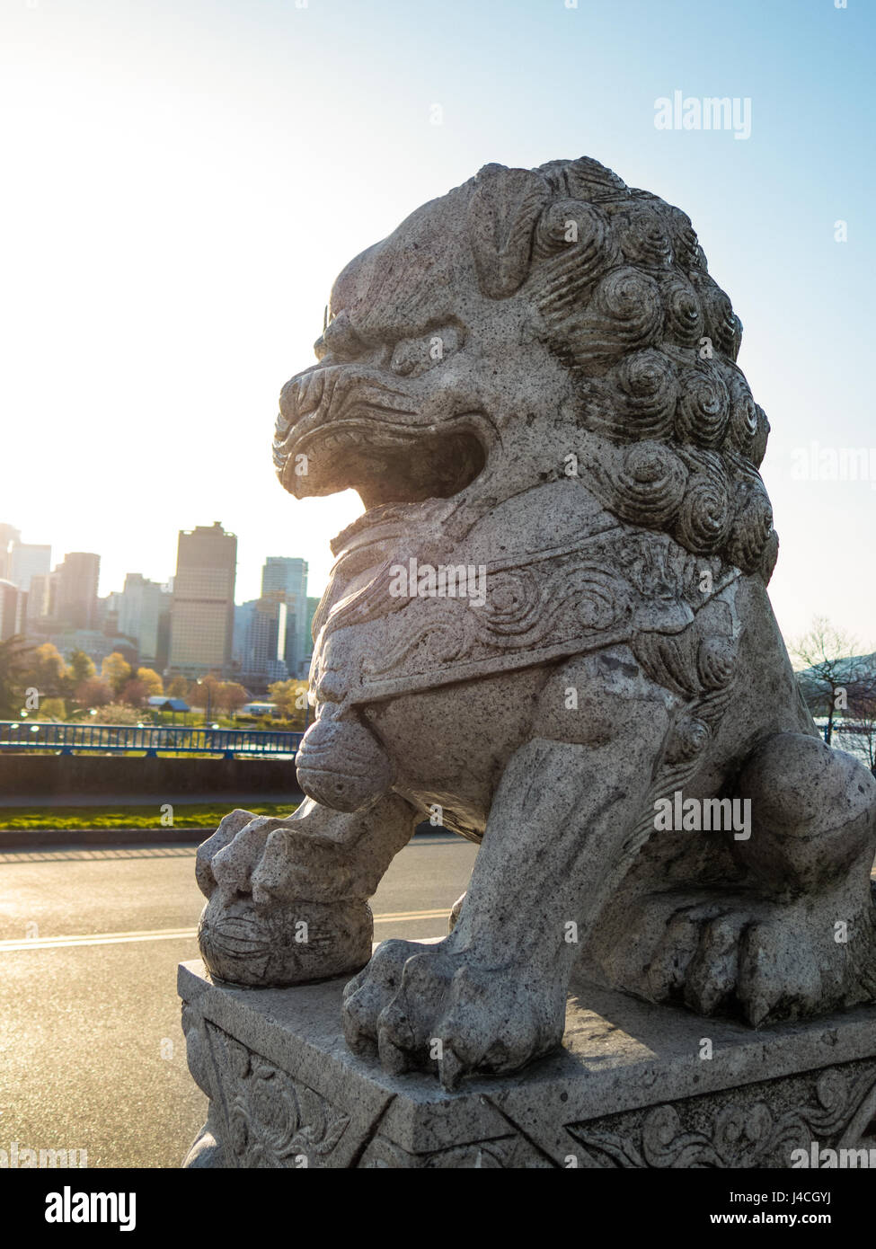 Foo Dog (Chinese Lion Guard) looking over Vancouver Skyline during sunset - Stock Image