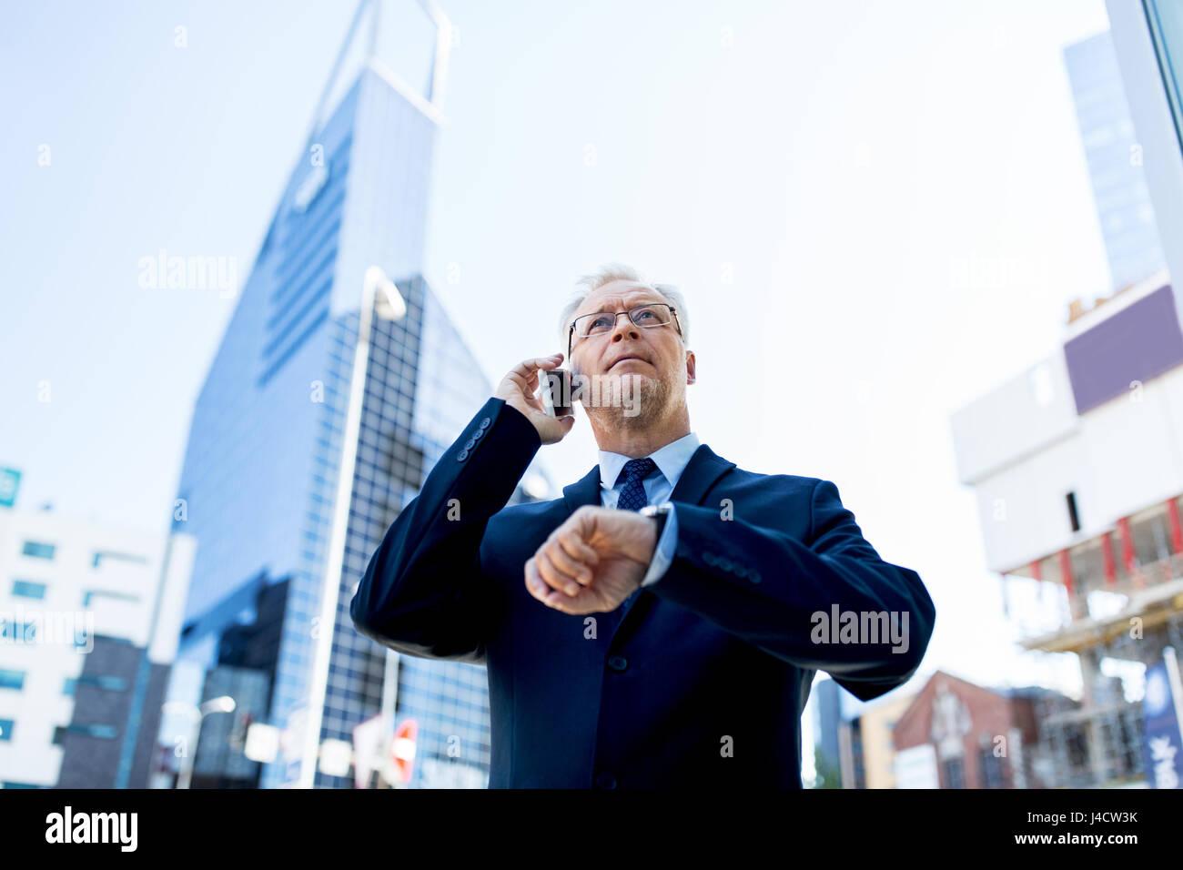 senior businessman calling on smartphone in city - Stock Image