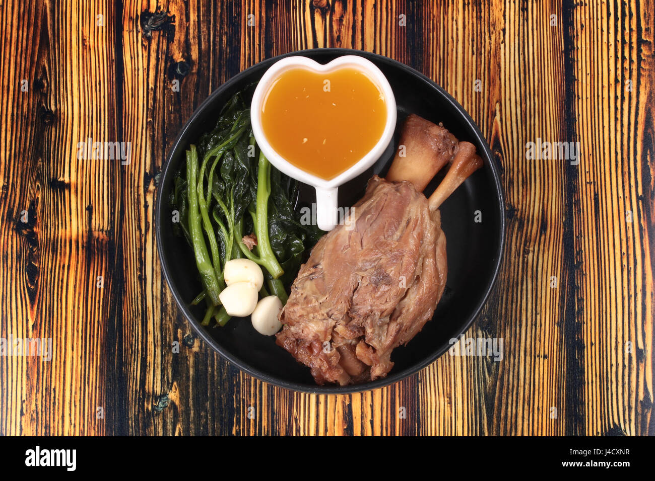 Fat out recipe of stewed pork, Stewed pork hock peel skin and fat out with boiled kale served on wood.  Call Kha - Stock Image