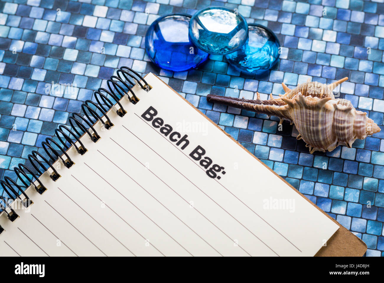Summer beach bag, picnic, camping, packing, travel, itinerary list concept on notebook and wooden board - Stock Image