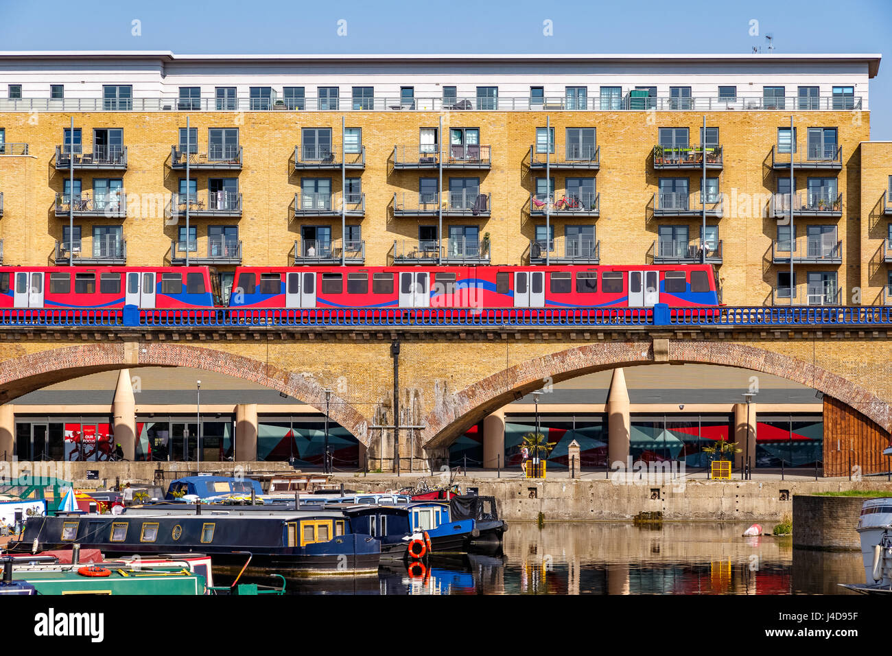 Waterside apartments at Limehouse Basin Marina in London with Docklands Light Railway passing by - Stock Image