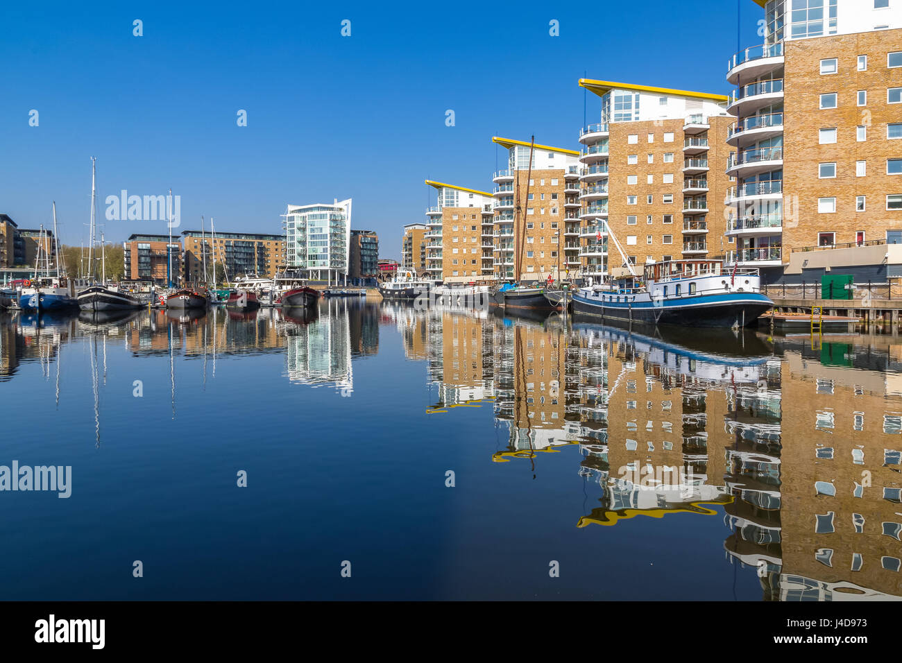 Waterside apartments at Limehouse Basin Marina  with Docklands Light Railway passing in the background - Stock Image