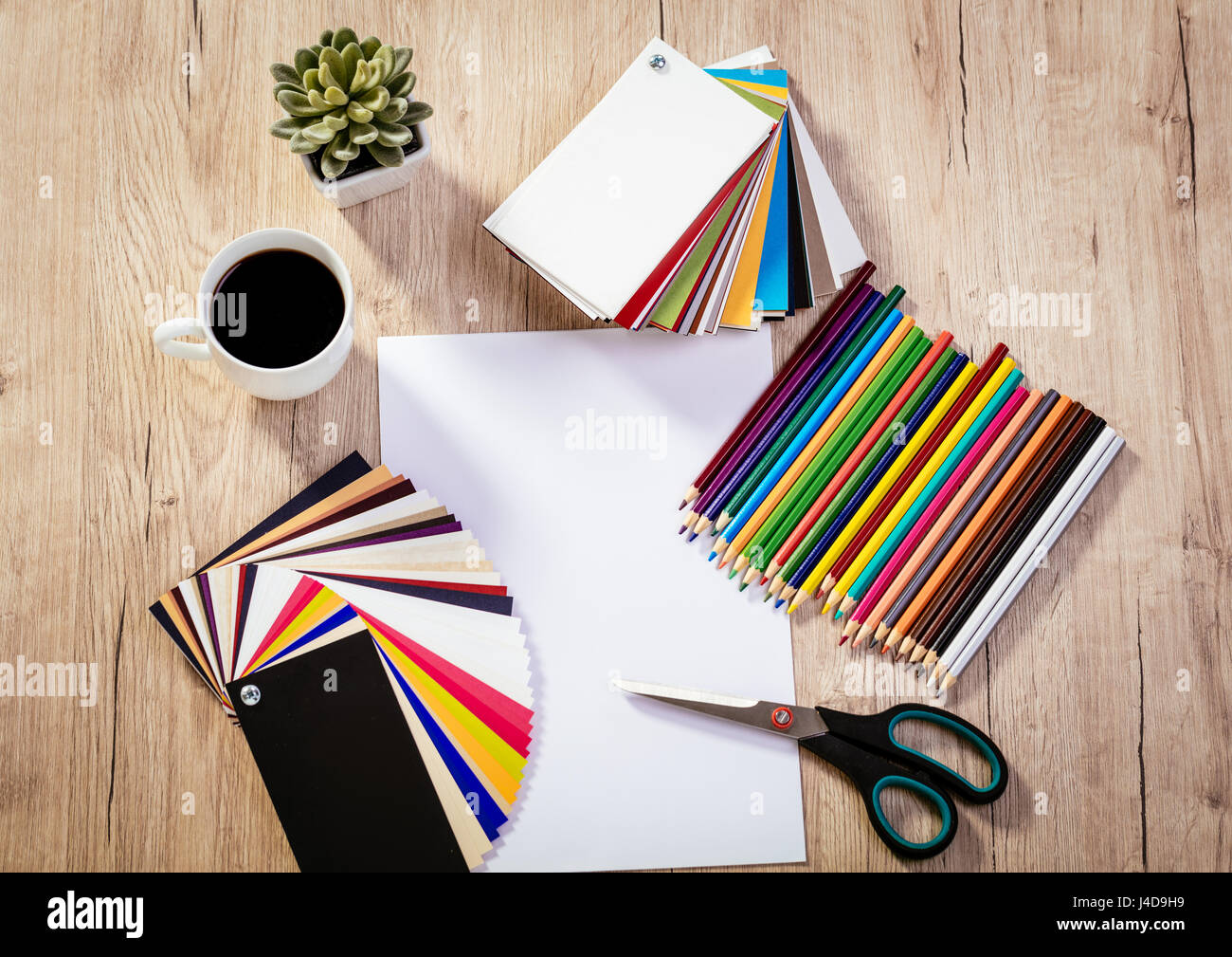 Top View Of A Designer Workspace With Blank Paper And Pallete Color.  Different Office Accessories And Cup Of Coffee Is On The Table.