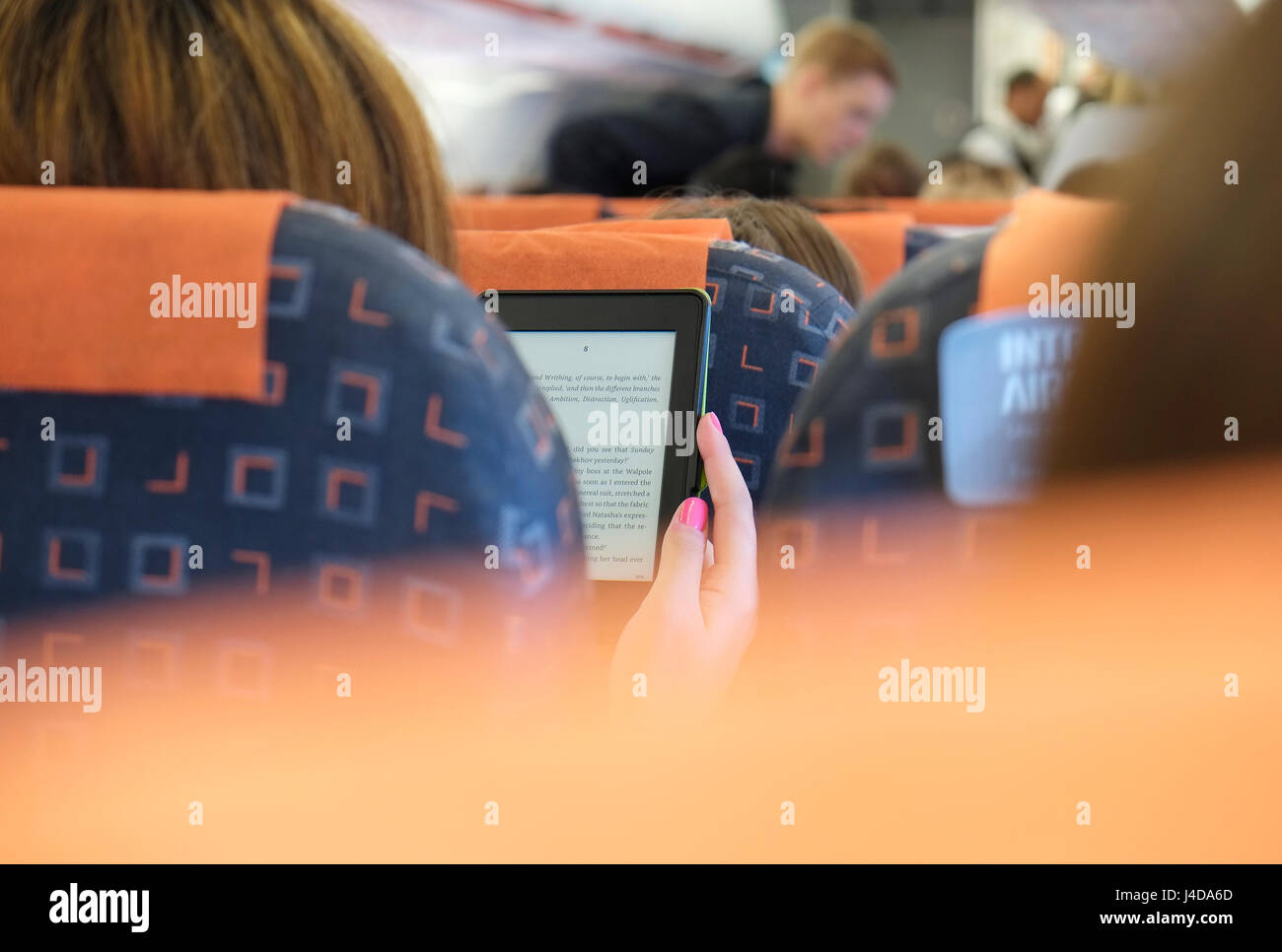 person reading ebook on aircraft flight - Stock Image