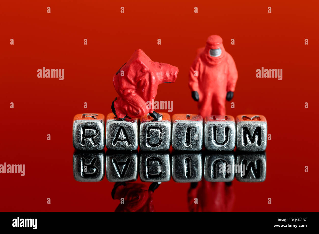 Miniature scale model team in chemical suits with the word radium on beads - Stock Image