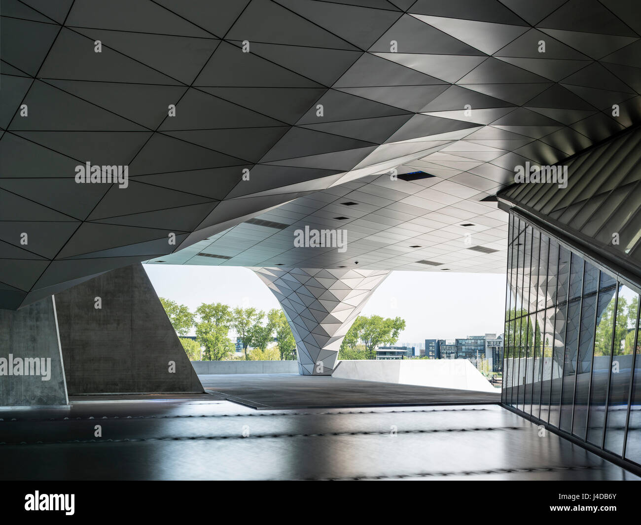 View of the public space underneath the building with illuminated pool. Musée des Confluences, Lyon, France. - Stock Image