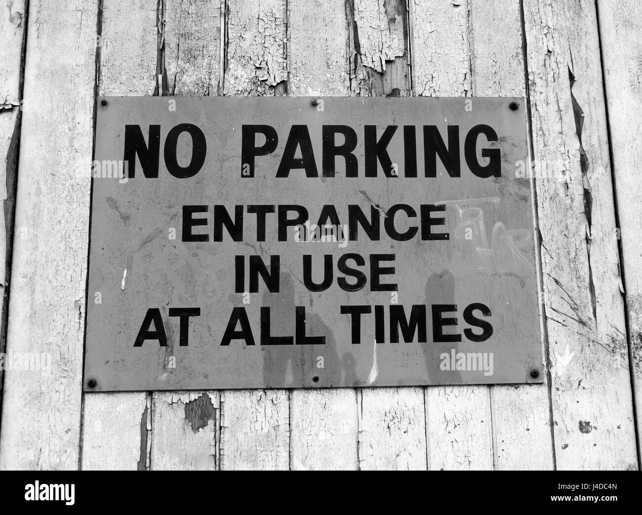 Monochrome faded no parking entrance in use at all times sign on dilapidated timber plank wall with flaking paintwork - Stock Image