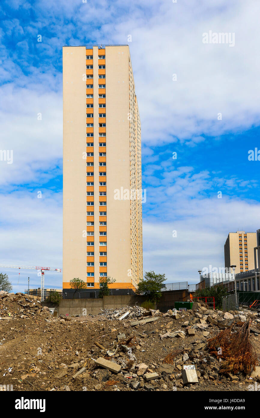 Block of hi-rise flats about to be demolished and standing alone in the rubble of other demolitions, Glasgow, Scotland - Stock Image