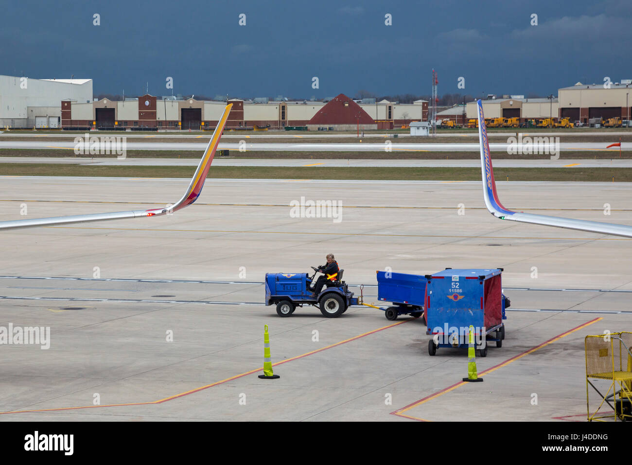 Detroit, Michigan - A Southwest Airlines baggage handler drives luggage carts as a storm threatens at Detroit Metro - Stock Image