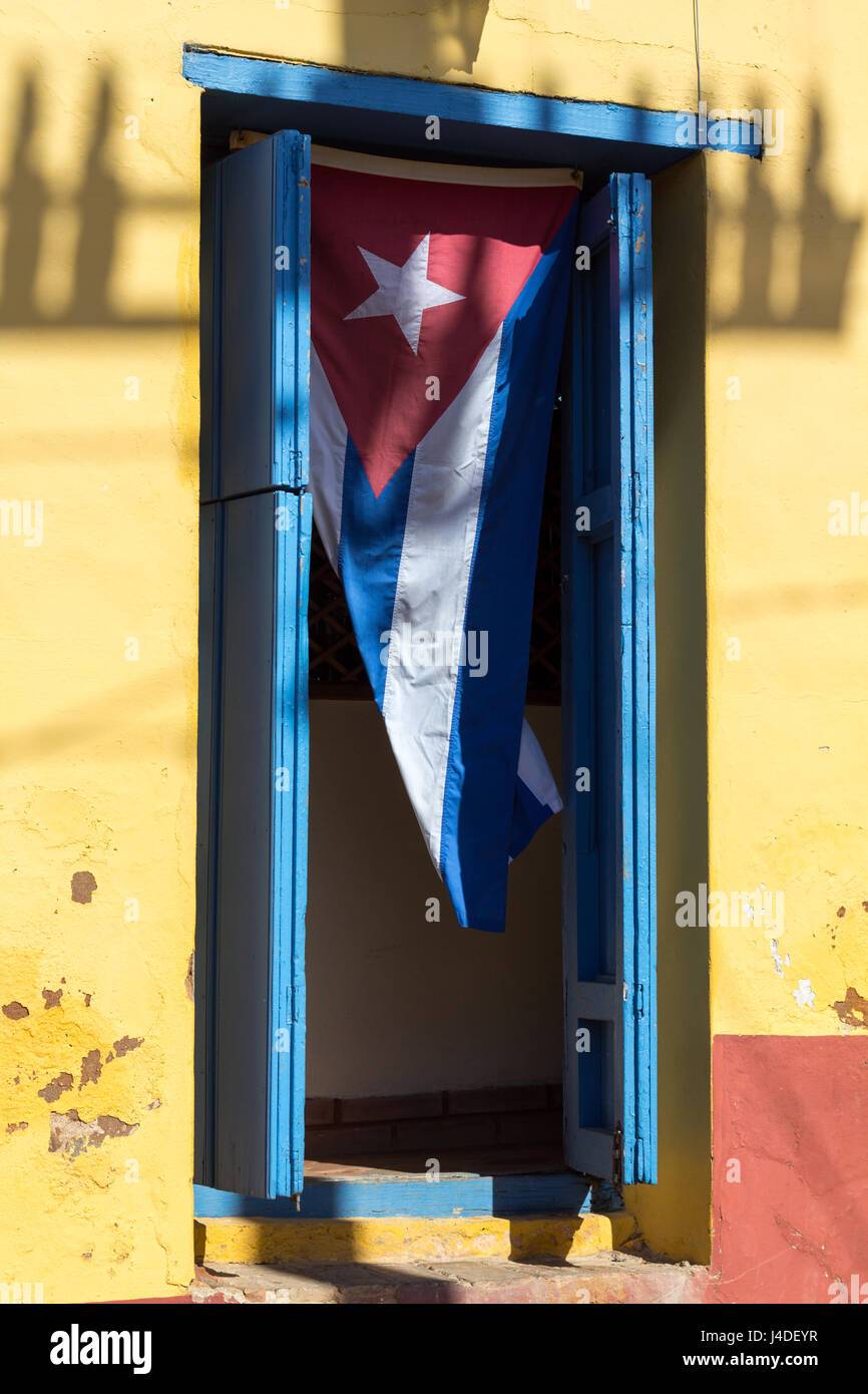 Cuban flag hangs vertically in an open doorway to a house in the UNESCO-protected part of Trinidad, Cuba - Stock Image