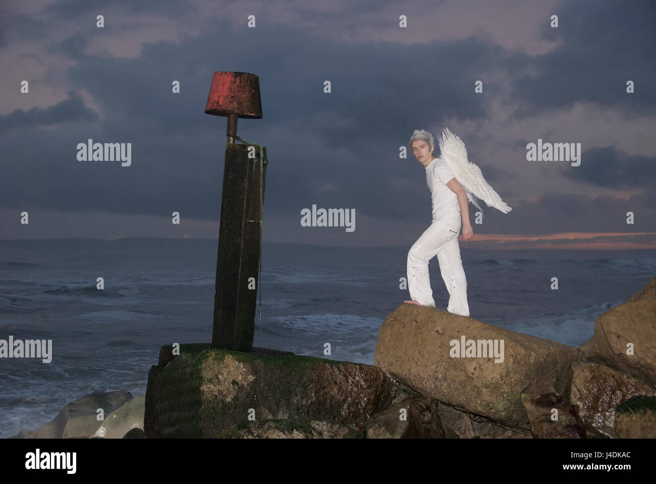 Young man dressed in white with angel wings on the rocks by the sea in stormy weather - Stock Image