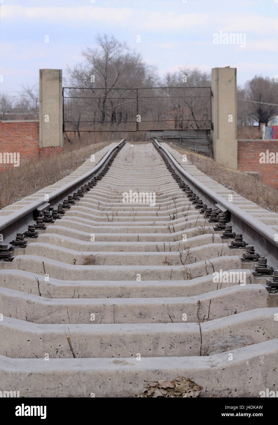 Railroad tracks leading to a metal gate in the city of Zhaodong China in Heilongjiang Province on an overcast day. - Stock Image