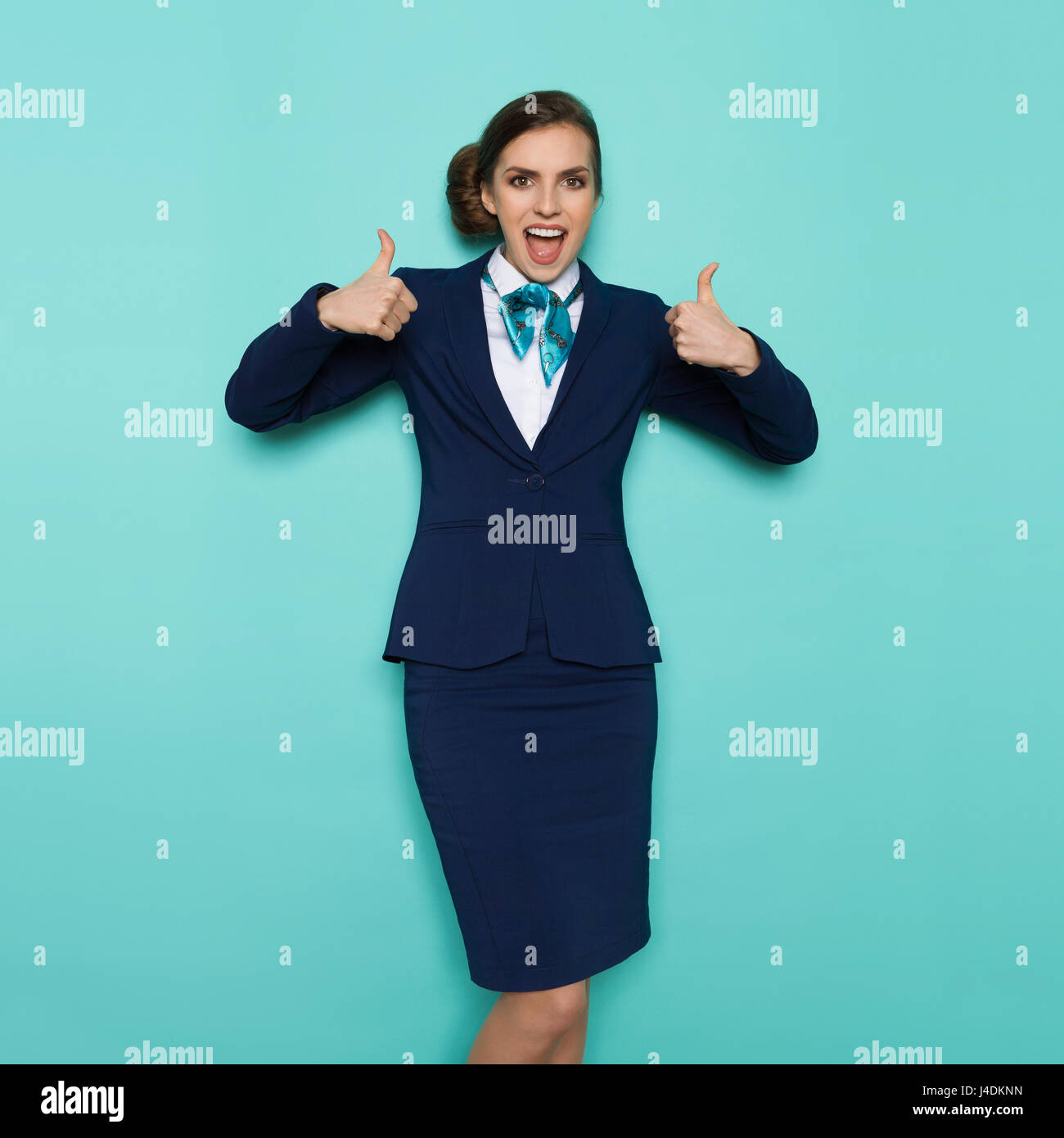 Excited stewardess in blue formal wear is standing with hands raised, showing thumbs up, shouting and looking at - Stock Image