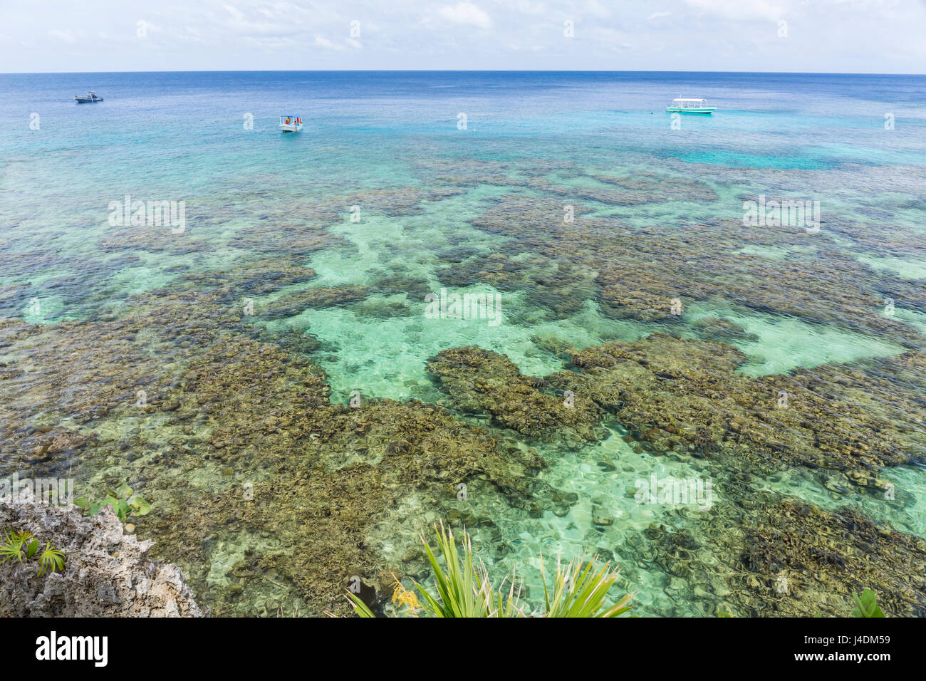 Dive boats in the crystal clear waters just off the Iron Shore of the Roatan barrier Reef in West Bay, Roatan, Honduras - Stock Image