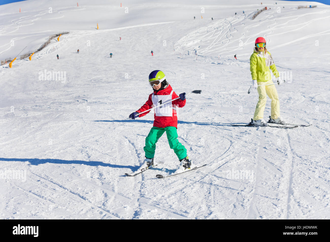 Boy learning downhill skiing with instructor - Stock Image