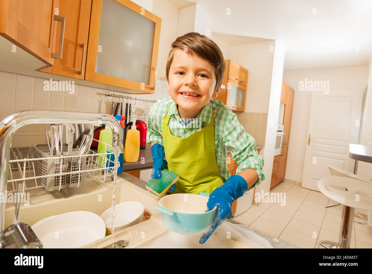 Cute Kid Boy Doing The Dishes In Rubber Gloves Stock Photo
