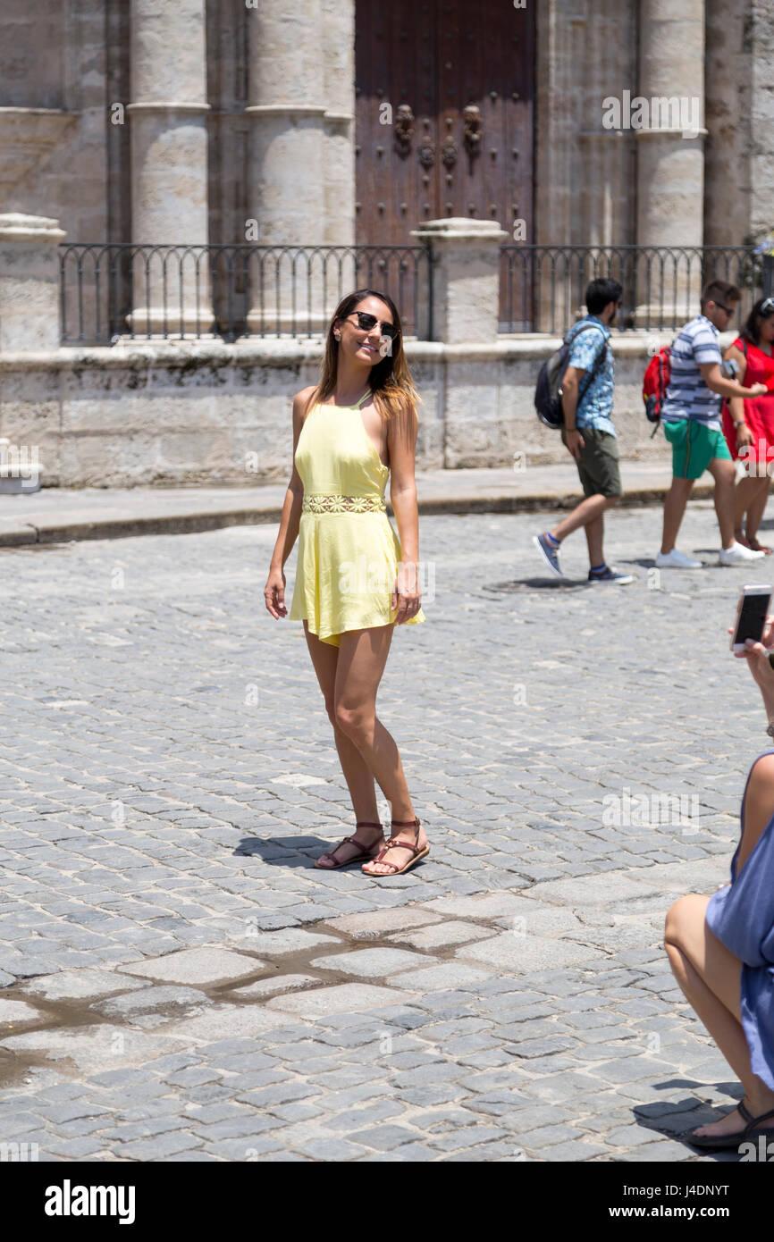 Young woman in yellow dress walking through Havana, Cuba Stock Photo
