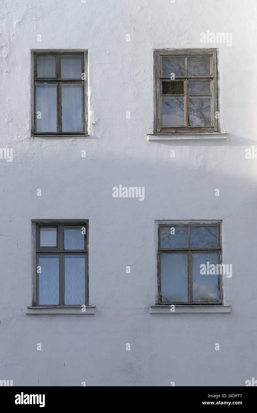White stucco wall house with four windows with old wooden vintage ...