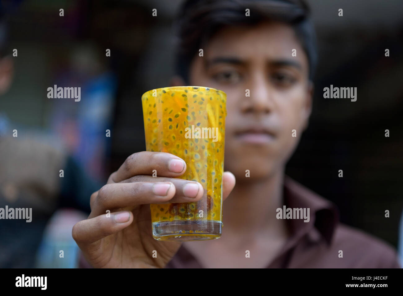 DHAKA, BANGLADESH - MAY 13, 2017: On a summer day a Bangladeshi boy drinks a glass of unhygienic cold fruit juice - Stock Image