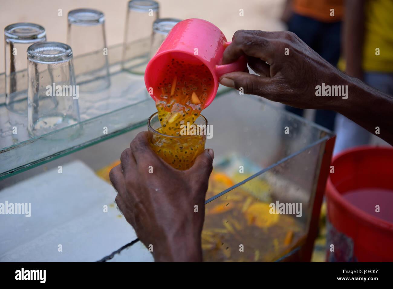 DHAKA, BANGLADESH - MAY 13, 2017: A Bangladeshi street vendor sells unhygienic cold fruit juice in Dhaka, Bangladesh. Stock Photo