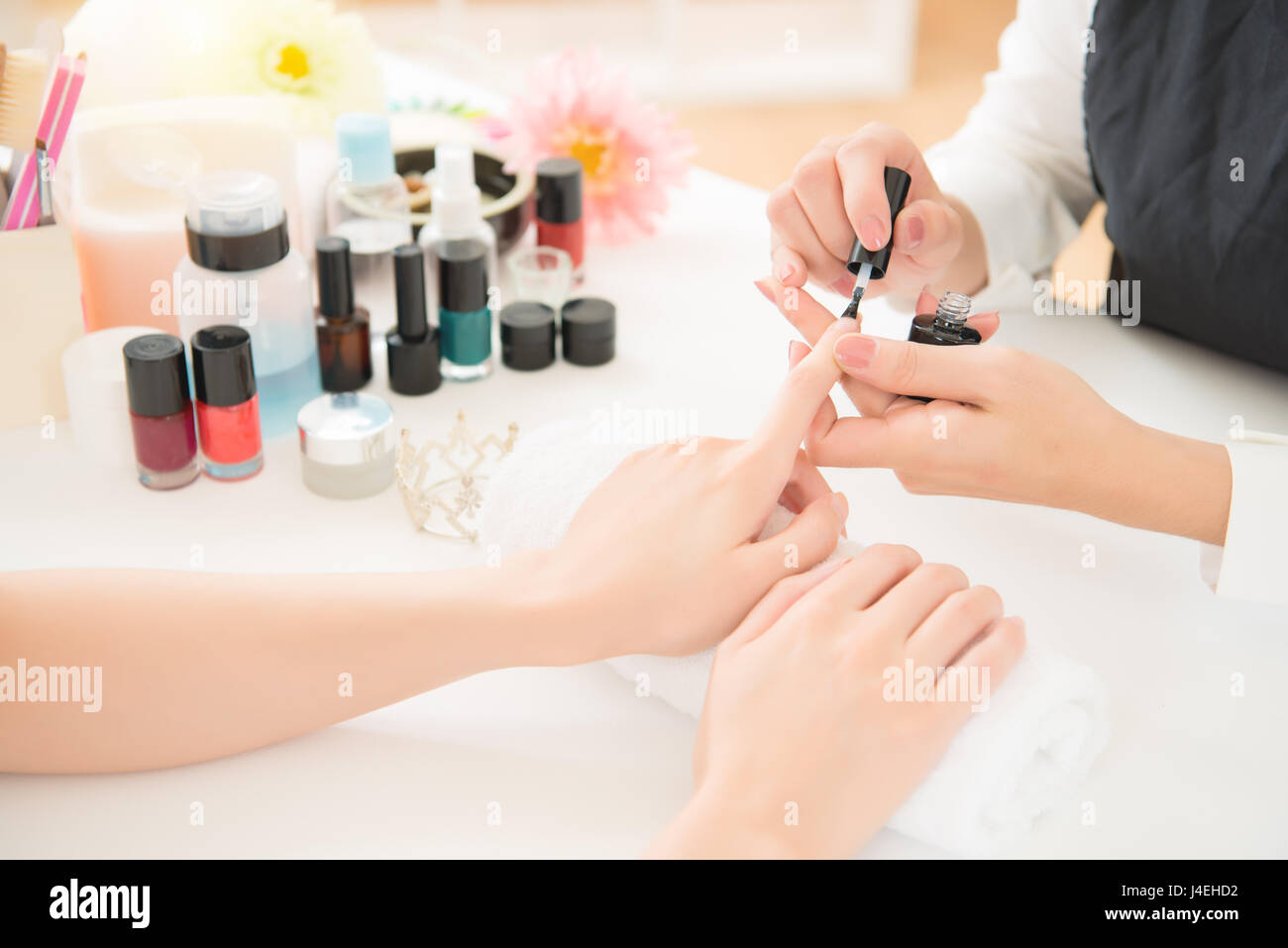 closeup of beautiful female hands applying transparent nail polish