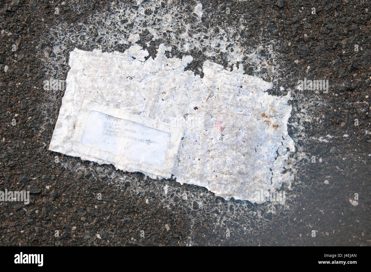 Scarcely recognisable as such, an unopened letter lies discarded on a suburban road - Stock Image