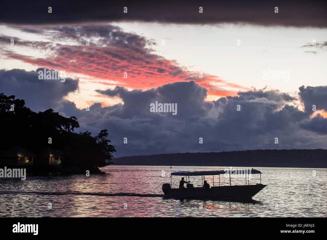 Tourist boat driving back home at sunset in Port Vila, Efate, Vanuatu, Pacific - Stock Image
