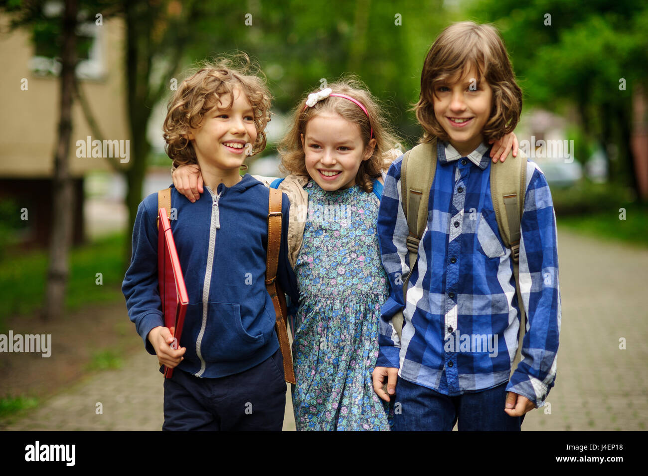 Three little school students, two boys and the girl, stand in an embrace on the schoolyard. Children's friendship. - Stock Image