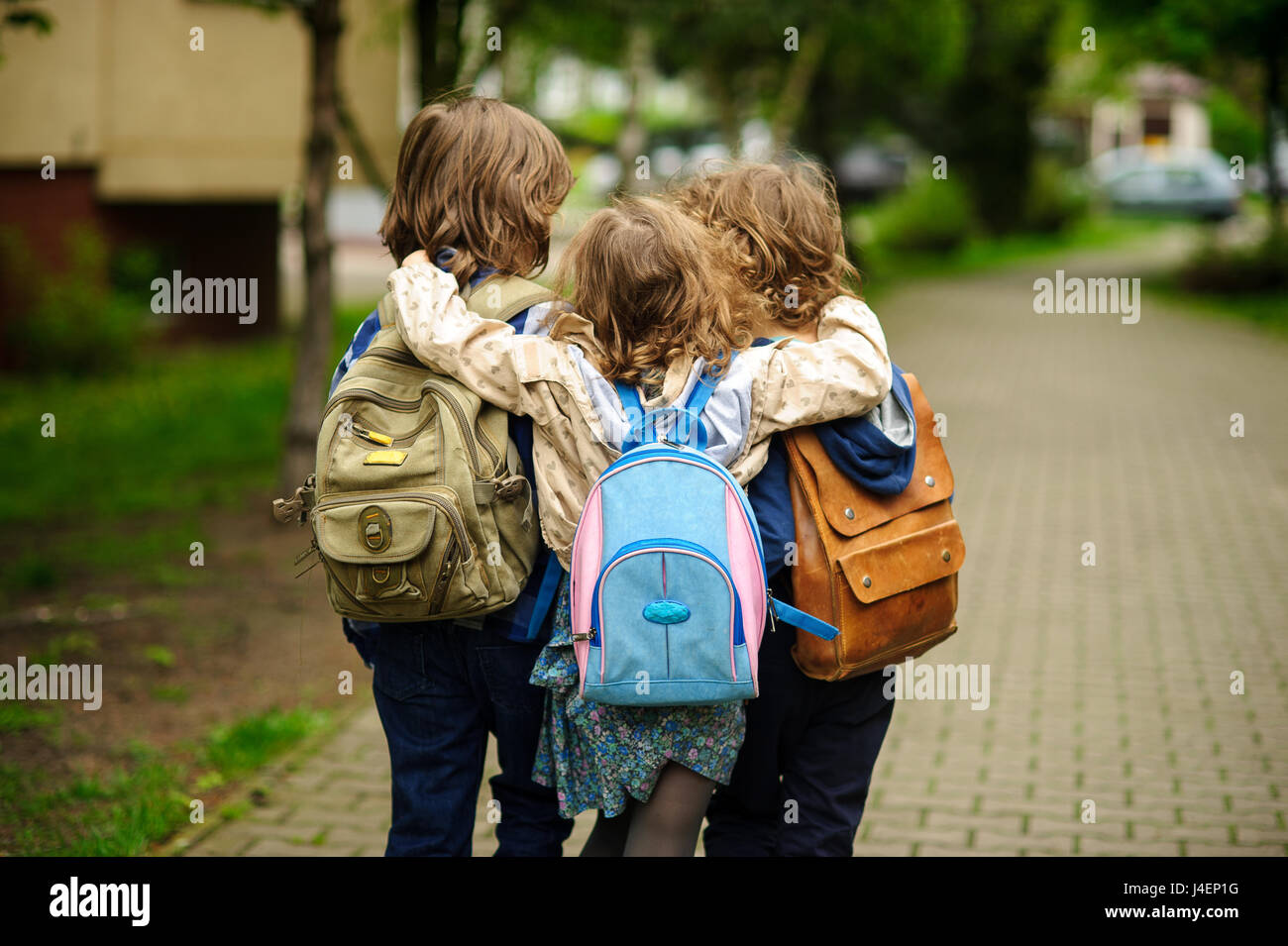 Three little school students go in an embrace to school. Children's friendship. - Stock Image