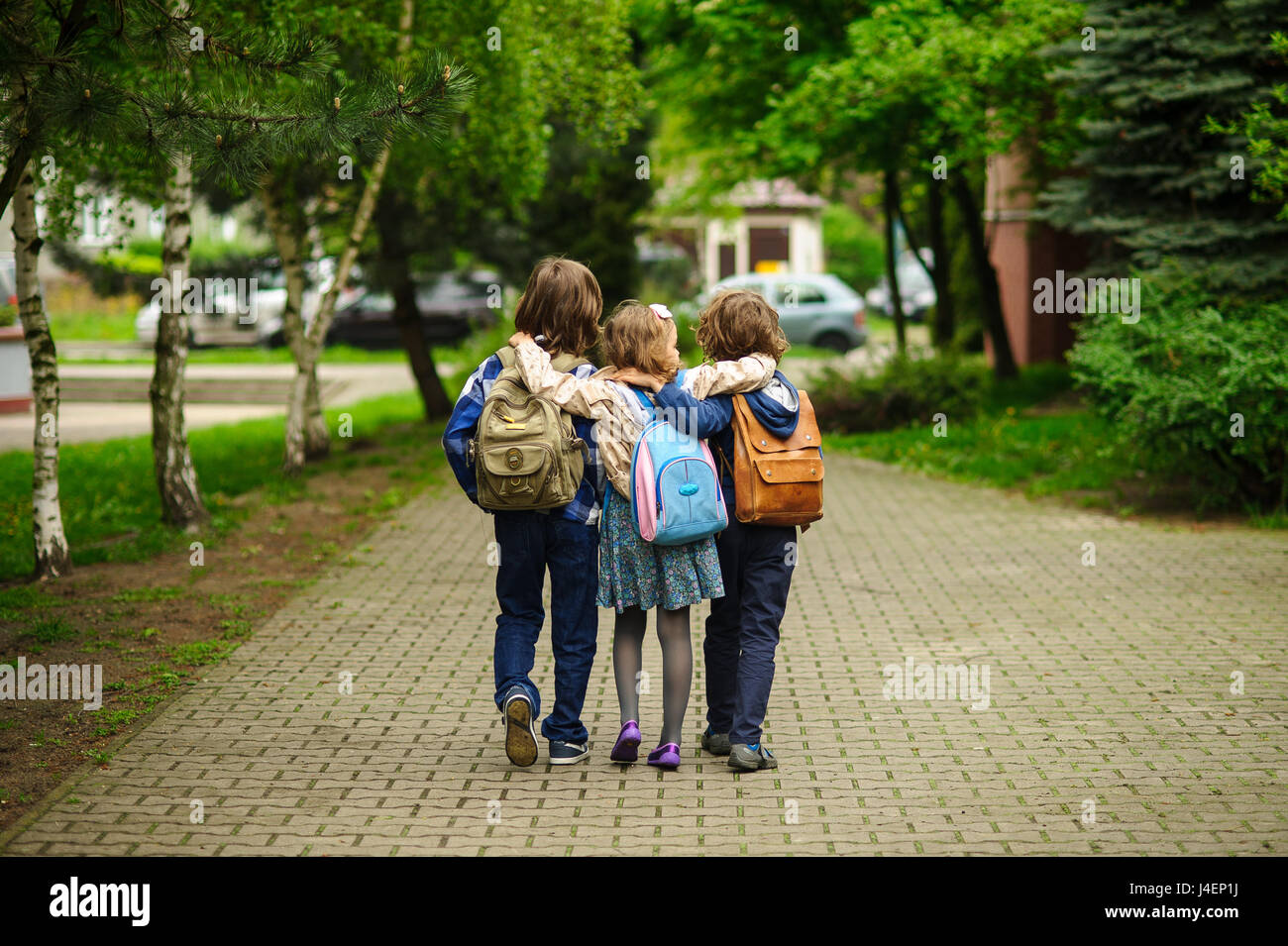 Three little school students, two boys and the girl, go in an embrace to school. Children's friendship. Serene - Stock Image